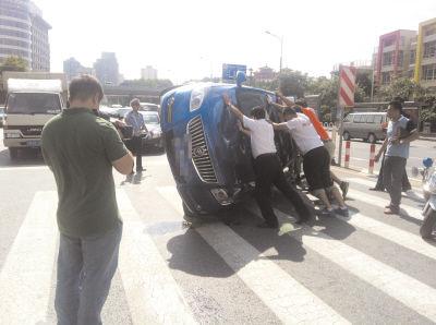 过往车辆的司机和行人将侧翻的轿车扶正