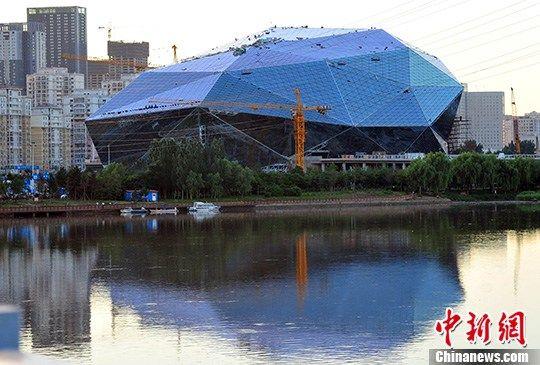 """7月21日,""""巨钻""""建筑沈阳文化艺术中心玻璃幕墙安装已近尾声。中新社发 于海洋 摄"""