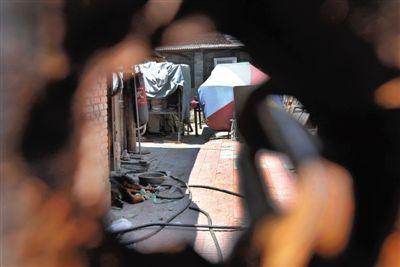 7月23日,被告人姜凡囚禁他人4年的院子,院子大门紧锁,透过大门可以看到院子杂乱的物品。新京报记者 王贵彬 摄