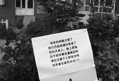 """网友反映,在沈阳于洪区北美家园小区内,不少车辆被划伤,有人写上""""诅咒语""""挂在车位附近。"""