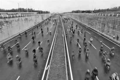 7月28日上午,沈阳新建成的四环快速路迎来了首批体验者,自行车爱好者在蒙蒙细雨中展开骑行。 本版照片由北国网、辽沈晚报首席记者 查金辉 摄
