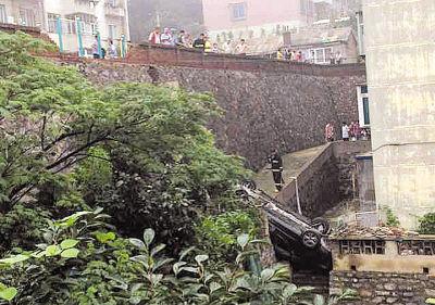 一辆黑色奔驰轿车四轮朝天,掉在约10米高的挡土墙下。