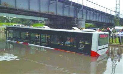 昨早,大雨过后,一辆公交车被困马总屯公铁桥下深水中。救援人员用梯子在车窗和桥沿之间搭6米长通道,把乘客一个一个送上岸。 消防供图