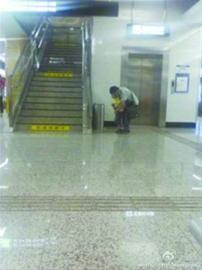 """昨晚7时30分许,微博网友""""代景阳""""发布了一条微博,看到在地铁二号线市图书馆站,有一位男子抱着儿子站在垃圾箱上上厕所,非常不文明。 网友供图"""