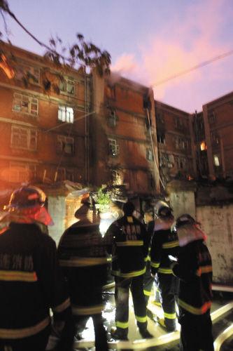 消防队员一边灭火一边疏散居民。