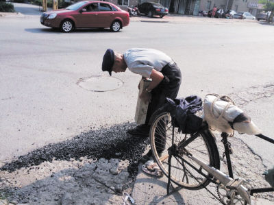 """老人顶着烈日,在路边找到一块长条青石,充当起""""压路机""""修补地上的坑洼,汗流浃背。(图由网友提供)"""