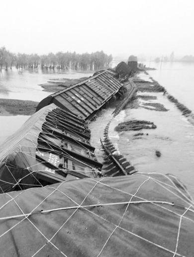 12日,在绥北线扎音河至海伦间,因降雨引发洪水冲毁路基,一列货物列车脱线。新华社发