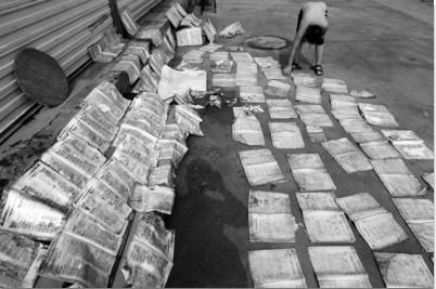 昨日下午,在新宾南杂木镇,一家门市前晾晒着许多湿透的学生作业本。