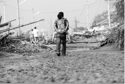昨日下午,在南口前镇,一位群众背着孩子穿过泥泞的铁北街向安置点方向走去。