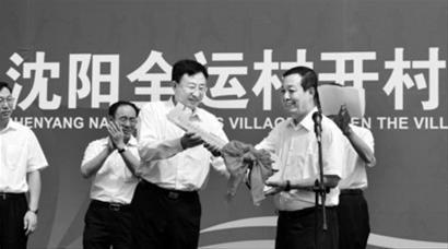 沈阳市市长陈海波(前左)向全运村村长杨亚洲交付全运村钥匙。