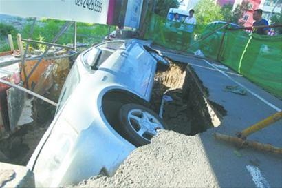 沈阳杏林街药王庙路交通岗附近,周五暴雨当天路面塌陷掉入大坑的轿车仍躺在坑中。 北国网、辽沈晚报记者 纪力元 摄