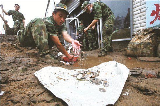 """武警官兵帮助邮政储蓄所清理淤泥,""""抢救""""被淤泥掩埋的现金和票据"""