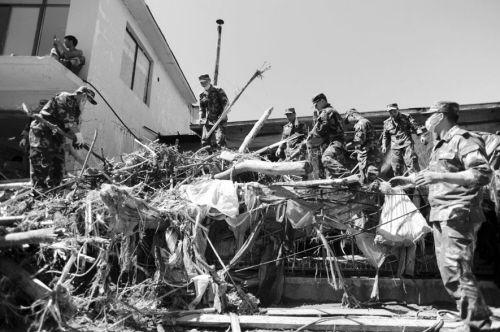 战士们挥舞着手中的铁锹,为村民清除屋子中两米多深的淤泥。