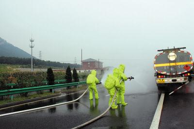 消防人员正在给拉盐酸的槽罐车喷水稀释。