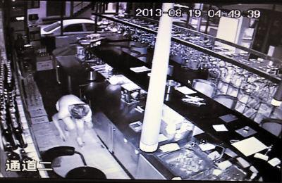 男子只穿了一条内裤,在脑袋上套个塑料袋,轻手轻脚地走到收银台附近。