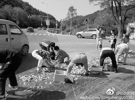 市民捡掉在地上的鱼