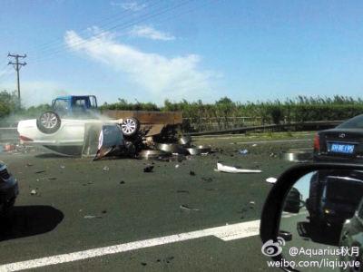 事故现场一片狼藉,白色轿车被撞翻。