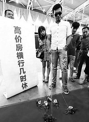 """19日,一位小伙子用绳子牵了好几只螃蟹出现在南京秋季房展会上,螃蟹壳上贴有""""高地价""""""""高房价""""字样,寓意高房价和高地价""""横行"""",被网友称为""""遛蟹哥""""。"""
