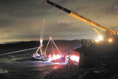 昨晚摄影记者赶到事发海边时,一艘被困船只停在岸边,因船内进水,几名男子正在往外舀水,吊车准备将船吊上岸。图首席记者李传报