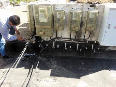 工作人员在公建商铺的房顶对电线进行检查,以便维修。