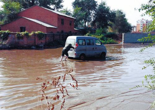 一辆微型面包车在千山西路的积水中熄火
