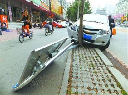 """两天前,沈阳市华山路223号附近地下水管漏水,修复后路面回填不实成""""陷阱"""",一辆私家车为躲大坑,撞到路边大树上。北国网、辽沈晚报记者 王迪 摄"""