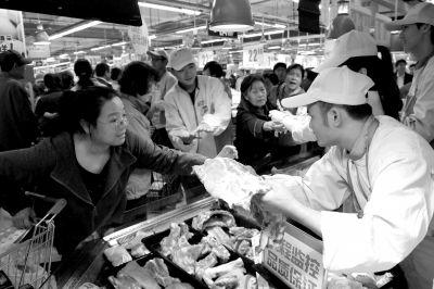 消费者在壹号土猪档口挑选猪肉