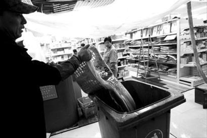 """大东区小商品大世界负一层A204档口,下水管道爆裂,粪水喷出,员工正在用临时做的""""盆""""向垃圾桶内清掏粪水。"""