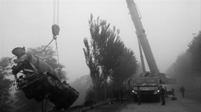 昨日早晨6时许,在沈阳市于洪区大坝路附近,一辆黄色的大罐车开进深20多米的坑里,吊车正在将大罐车吊起。北国网、辽沈晚报见习记者 胡月梅 摄