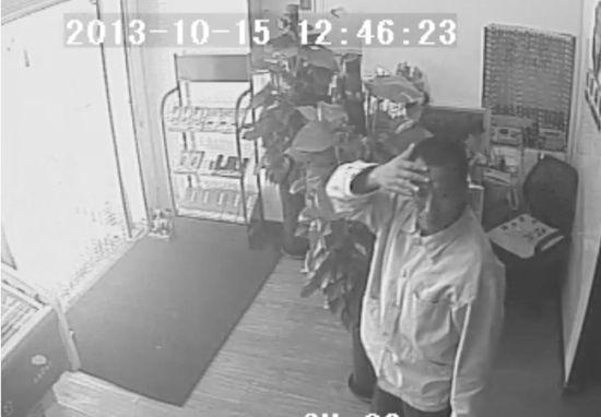 可疑男子溜进店面,用手挡脸