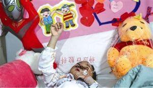 东东的病床上放着幼儿园小朋友做的爱心牌,上面贴着许多纸条,祝福东东早日康复