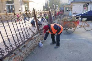 环卫工人丁大姨每天都要在小学的院墙外捡拾学生扔的垃圾。记者 王舜天 摄