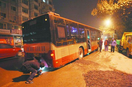 """一辆公交车在此""""陷落""""。半岛晨报、海力网摄影记者孟楠"""