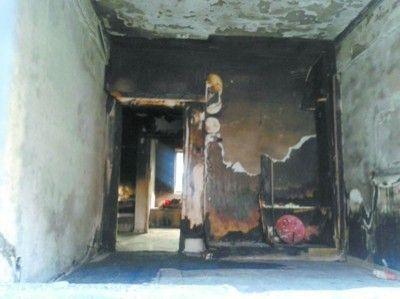 透过破碎的窗户看见过火的屋内几乎空无一物,墙壁也是黑漆漆一片。