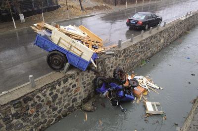 拖拉机头掉进路边的沟内,车斗被石柱卡在路面上。