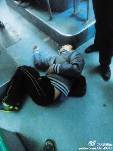 警察赶到后,打人者竟然躺倒在地拒绝起身。图由网友@大连蔚蓝 提供