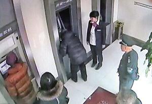 老人汇款时已经被银行的工作人员发现,随后丁行长赶到试图取消老人的操作■视频截图
