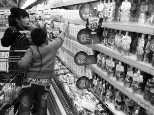 一超市内,家长带着孩子在选购奶制品。