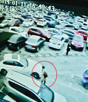 女子(红圈处)站在停车位前,不准正常停车的唐先生进入车位。