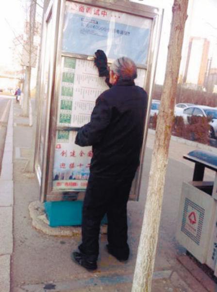 老人正用抹布擦站牌