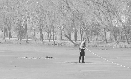 消防战士着单衣在冰面上拉绳救援。