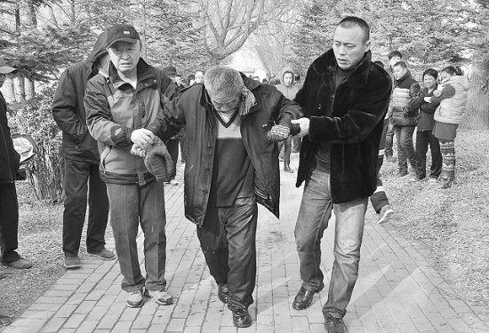 好心市民搀扶落水老人去上救护车。
