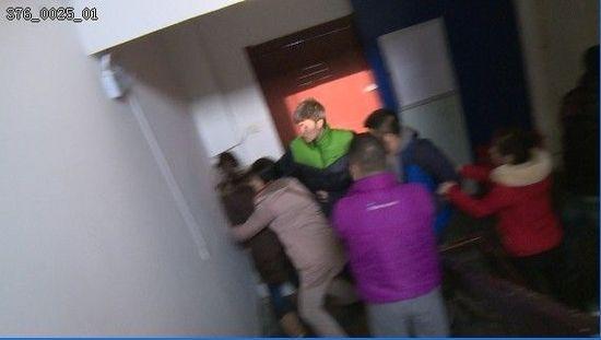 灰色大衣的女教师(左二)抢夺女记者(左一)的摄像机
