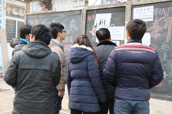 闻讯而来的人们在告示板上寻找相关信息