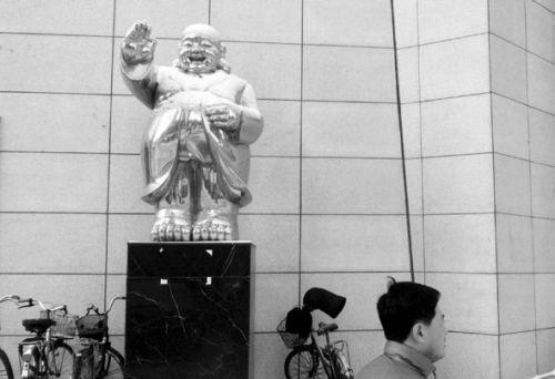 """北行""""穿风衣""""的弥勒佛雕塑。"""