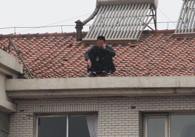 男子坐在楼顶打电话。