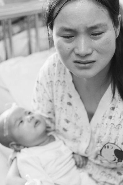 李忠霞疲惫地抱着大女儿,孩子小脑袋上还扎着针头。半岛晨报、海力网摄影记者阎昱颖