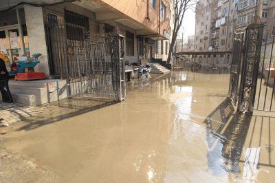 路边小区由于地势低洼,单元门被积水堵住了。
