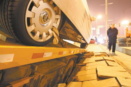 昨晚7时许,沈阳市青年大街劳斯莱斯专卖店门前发生地面塌陷,一辆拖车陷进坑里,所幸拖车上载有的价值500多万豪车安然无恙。