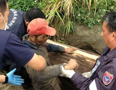 警消人员合力搬开棺材盖,将被关四天的简姓男子救出。